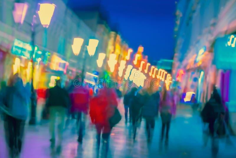 En lätt, suddig, modern stad på natten, avfokuserade stadsljus, silhuetter av gångande människor Sammanfattning arkivbilder