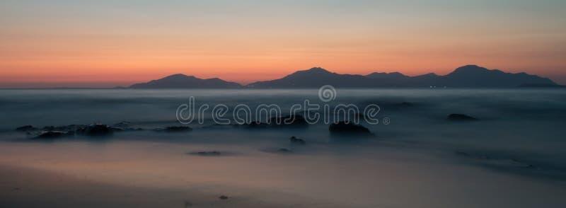 En lång exponering av havet på den guld- timmen, som solen ställer in bak ett berg arkivfoton