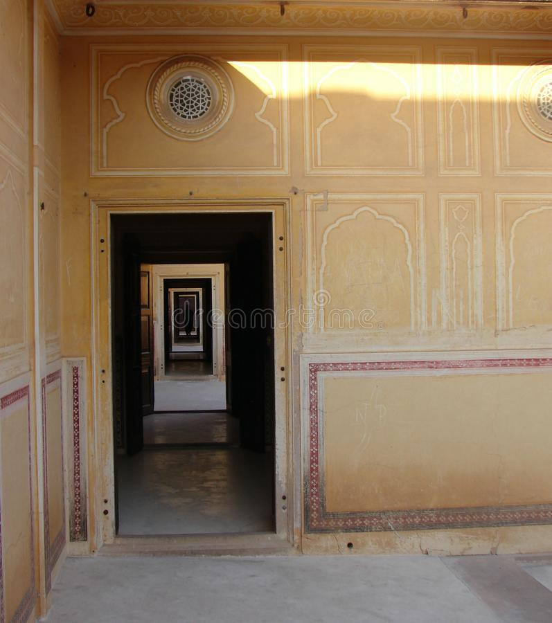 En lång korridor av rektangulära dörrar med en mänsklig kontur i mörker royaltyfri fotografi