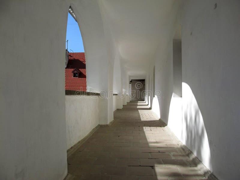 En lång korridor med välvda fönster och vita väggar på den Palanok slotten arkivfoton