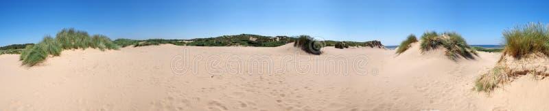 En lång panoramautsikt av gräs täckte kust- sanddyn framme av havet i formby merseyside på en ljus sommardag royaltyfria bilder