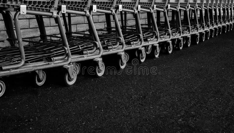 En lång rad av gamla shoppa vagnar längs en ställning för tegelstenvägg på asfalt som väntar för att återanvändas, skott i svartv royaltyfri foto