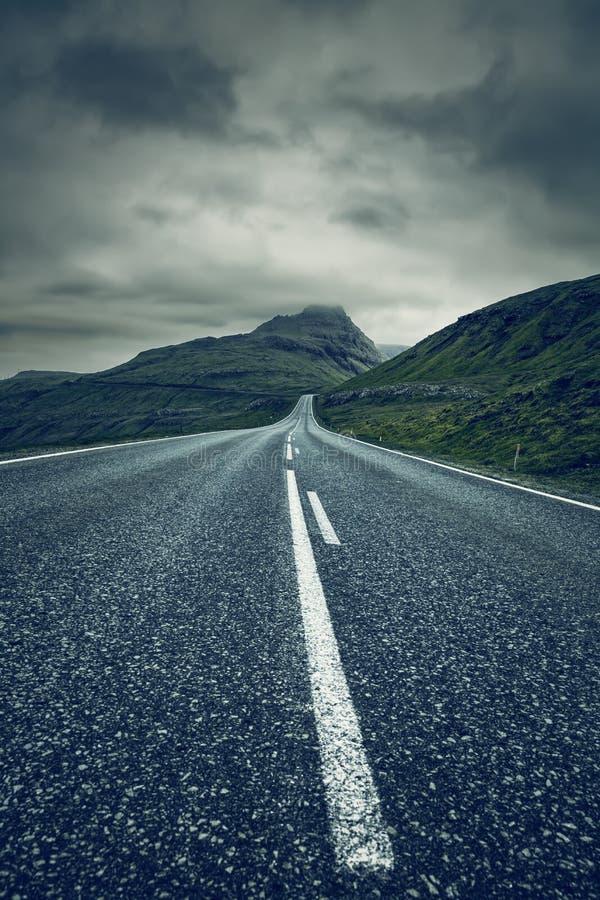 En lång tom rak väg, Faroe Island royaltyfri fotografi