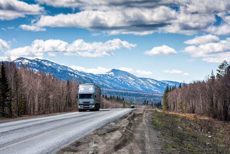 En långdistans- lastbil med en semitrailer flyttar sig på vägen bland bergen som täckas med snö arkivfoton