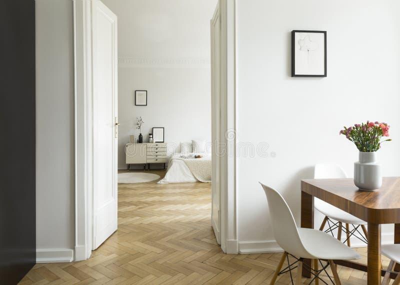 En långdistans- sikt från en matsal in i ett sovrum i en lägenhet för högt tak Monochromatic vit inre med fiskbensmönsterparqu royaltyfri bild