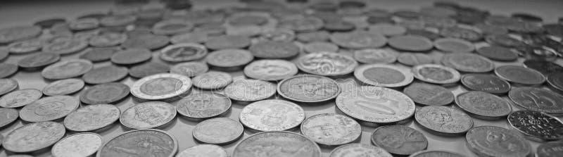 En långsträckt bild med mynt från olika valutor i svartvitt arkivbild