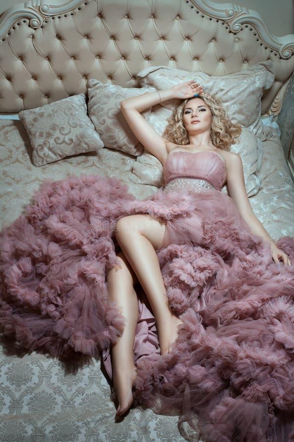 En la cama grande es la muchacha en un vestido magnífico fotografía de archivo
