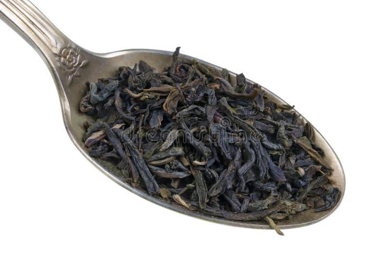 En la cuchara de oro vieja hay una pequeña pila de comida - macro aislada china seca del dragón de vuelo del té de verde de la él fotografía de archivo