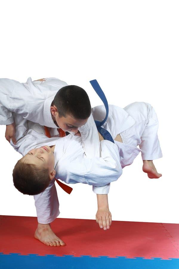 En la estera los deportistas están entrenando a tiros de judo fotografía de archivo