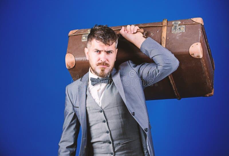 En la manera al ?xito hombre de negocios en corbata de lazo Hombre barbudo en traje formal Bolso pesado viajero maduro esthete el foto de archivo