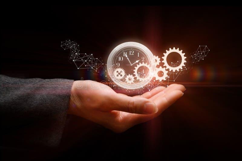 En la mano del hombre de negocios y del mecanismo de trabajo del reloj foto de archivo