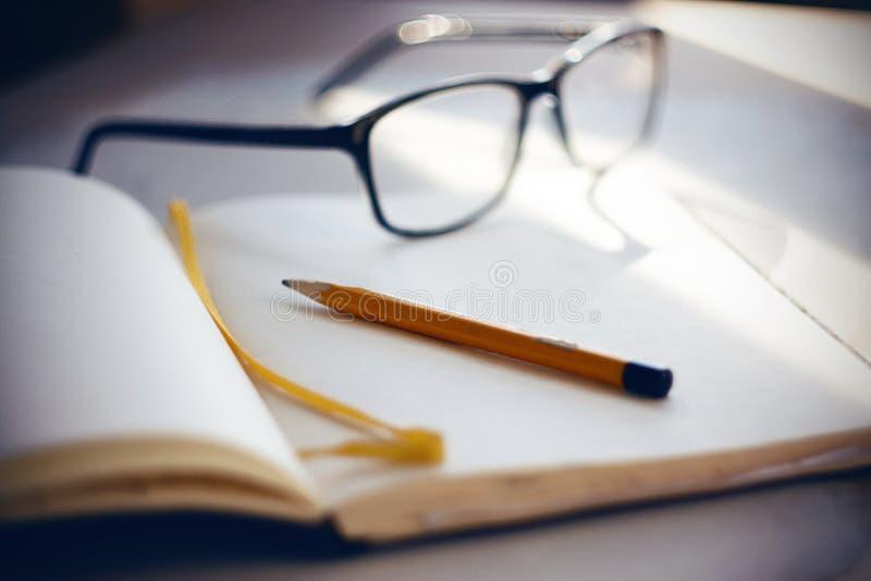 En la mesa son los vidrios, un cuaderno y un lápiz foto de archivo libre de regalías