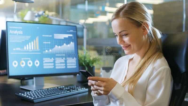 En la mujer atractiva Swirles de la oficina en silla, sonrisas y aplicaciones imágenes de archivo libres de regalías