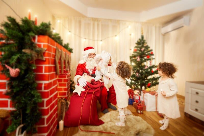 En la Navidad Santa Claus distribuye los regalos a los niños fuera de t imagen de archivo libre de regalías