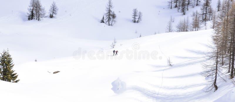 En la nieve de las montañas en las montañas, dos caminantes suben hacia los picos fotografía de archivo