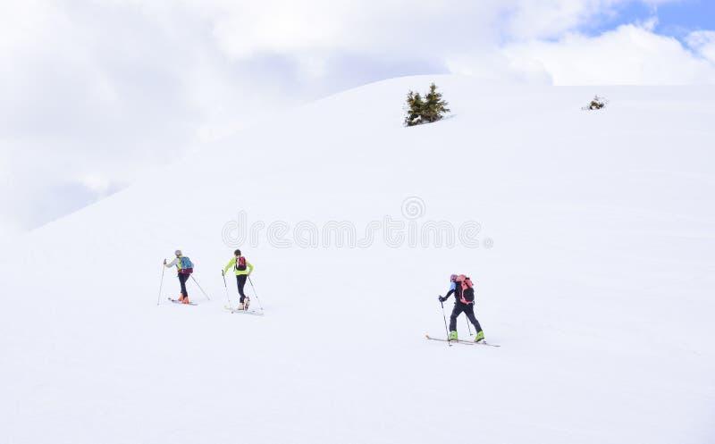 En la nieve de las montañas en las montañas, tres caminantes suben hacia los picos imágenes de archivo libres de regalías