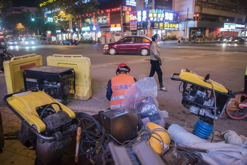 En la noche, un trabajador de construcción que se sienta en un sitio de la construcción de carreteras imagen de archivo libre de regalías