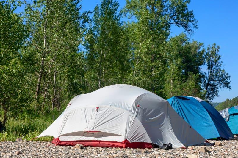 En la orilla cerca del bosque, un camping con las tiendas foto de archivo