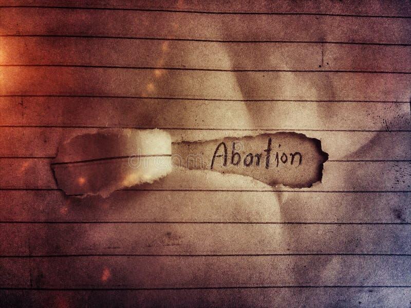 En la página cortada del papel el aborto de la palabra escrito detrás de la página siguiente fotografía de archivo
