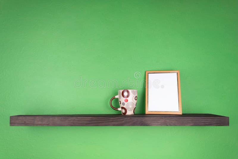 En la pared verde hay un estante coloreado oscuro con una taza y un marco de la foto en él fotos de archivo