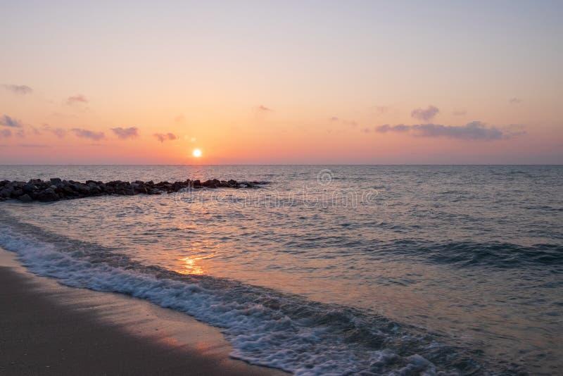 En la playa con las rocas que penetran hacia fuera en el mar a la hora de salida del sol imagen de archivo libre de regalías