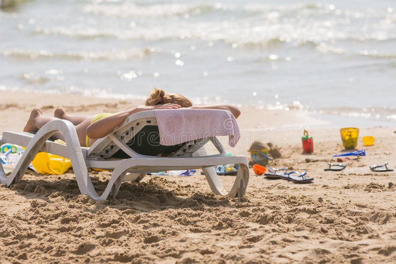 En la playa del mar cerca del agua con una silla de playa que toma el sol a la muchacha, el azote y la arena de los niños juega fotografía de archivo libre de regalías