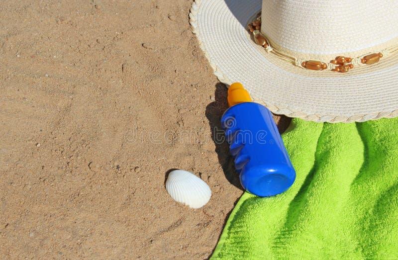 En la playa, el sunhat, la toalla y el sunmilk foto de archivo