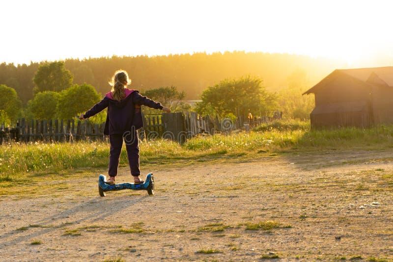 En la puesta del sol, una muchacha adolescente monta un hoverboard fotos de archivo libres de regalías