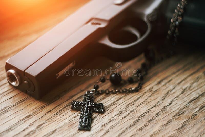 En la superficie de madera es un arma y un rosario con una cruz negra en una cadena imagenes de archivo