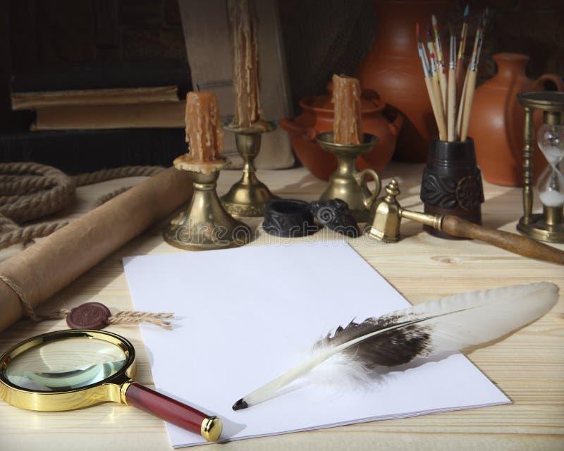 En la tabla de madera sea: una voluta con un sello, hojas del Libro Blanco, una pluma del ganso, un tintero, borlas, una lupa, b imagenes de archivo