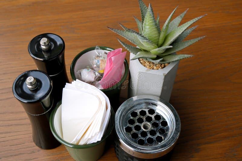 En la tabla en el café Pimienta, sal, azúcar, servilleta, cenicero, flor fotos de archivo