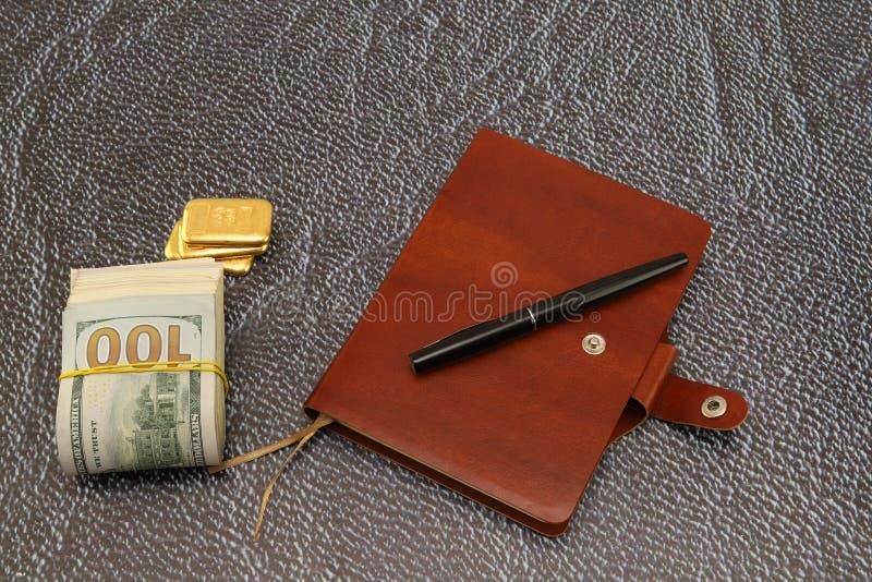 En la tabla es un paquete de dólares y de barras de oro Composici?n horizontal foto de archivo libre de regalías