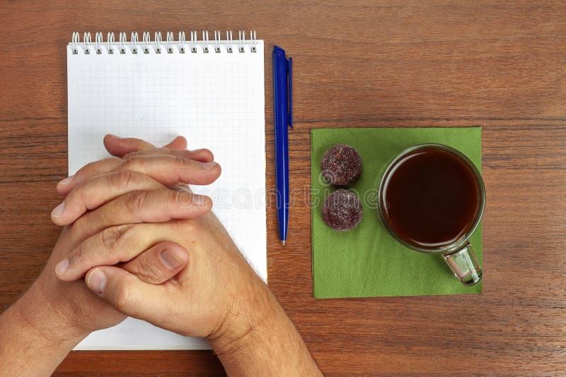 En la tabla miente una pluma, cuaderno, té, dulces durante negociaciones imagen de archivo