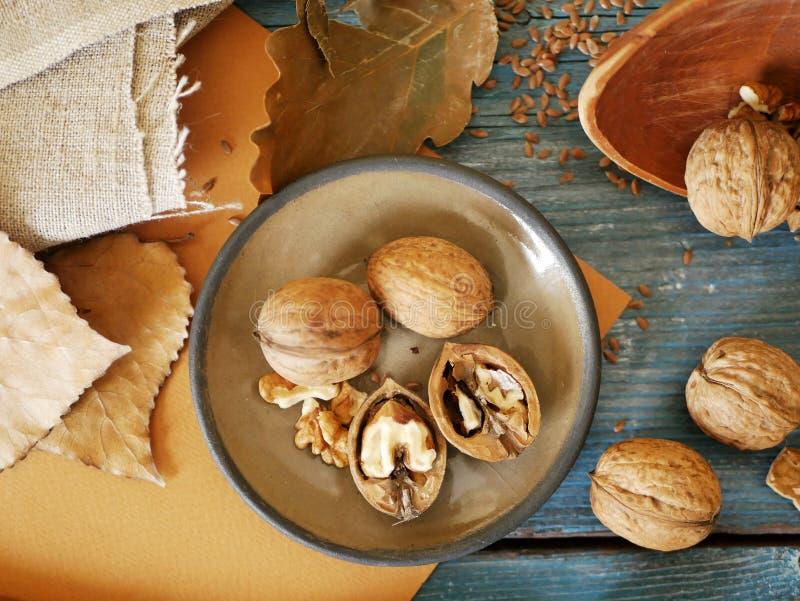 En la tabla, nueces, linaza, utensilios de madera, vintage, cocinando la comida sana fotos de archivo