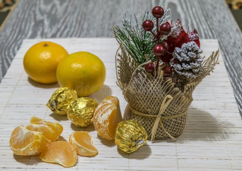 En la tabla son las rebanadas de mandarín, de caramelo y de decoración de la Navidad imagen de archivo