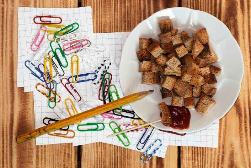 En la tabla en un lío de los clips multicolores dispersados para atar notas, trozos de papel para estudiar Está después una placa imágenes de archivo libres de regalías