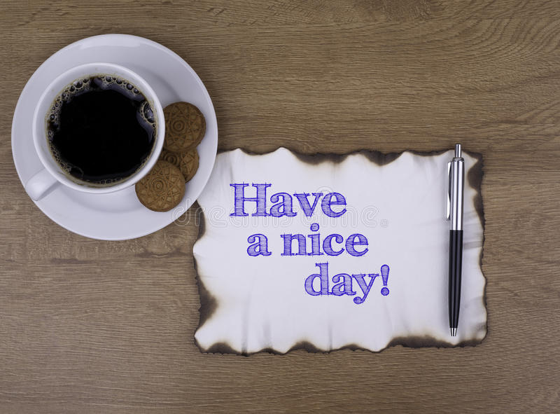 En la tabla un trozo de papel y un texto ¡Tenga un día agradable! foto de archivo