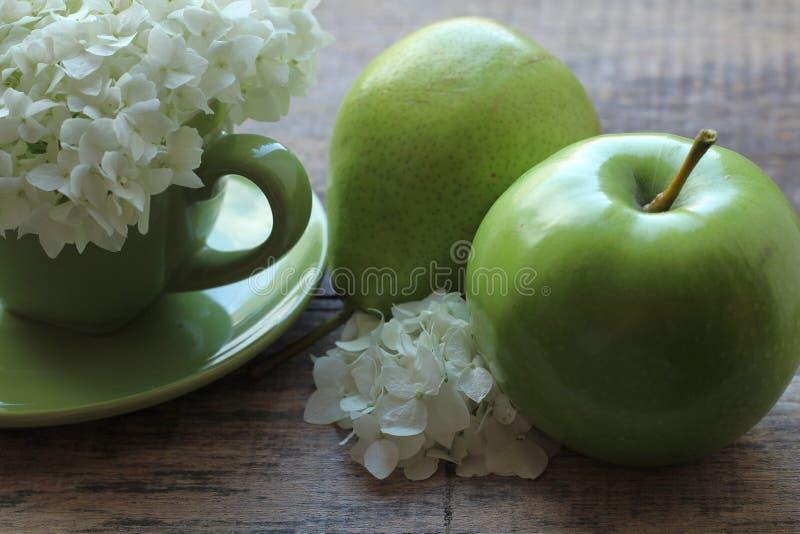 En la taza verde hay una inflorescencia magnífica de las flores blancas, y al lado de una pera verde con una manzana fotos de archivo