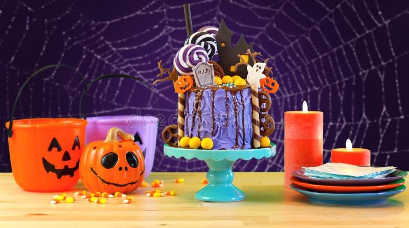 En la torta del goteo de la novedad del candyland de Halloween de la tendencia en el ajuste púrpura colorido del partido fotos de archivo