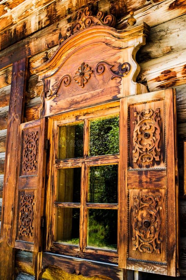 En la ventana de una casa de madera ventana abierta de los obturadores en una casa de madera en el campo Obturadores tallados de  foto de archivo