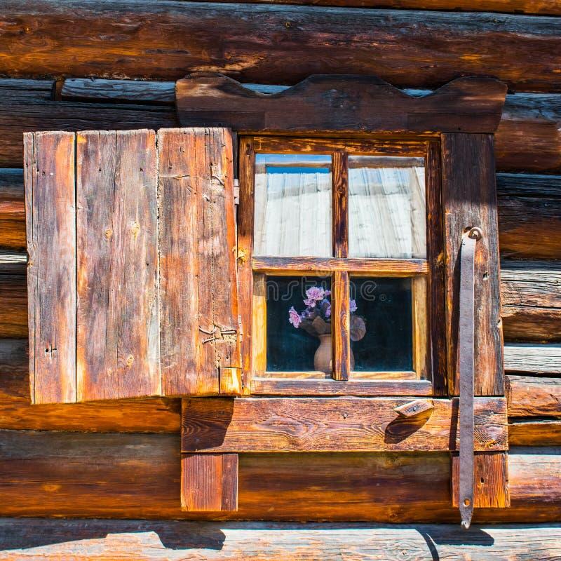 En la ventana de una casa de madera ventana abierta de los obturadores en una casa de madera en el campo imágenes de archivo libres de regalías