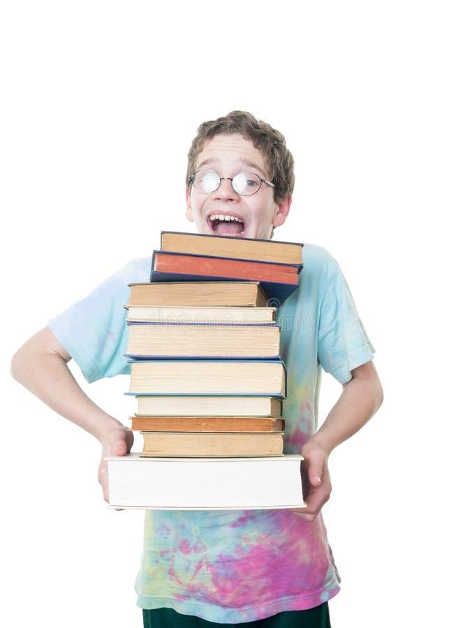 Den Teen pojken overloaded med bokar arkivbild