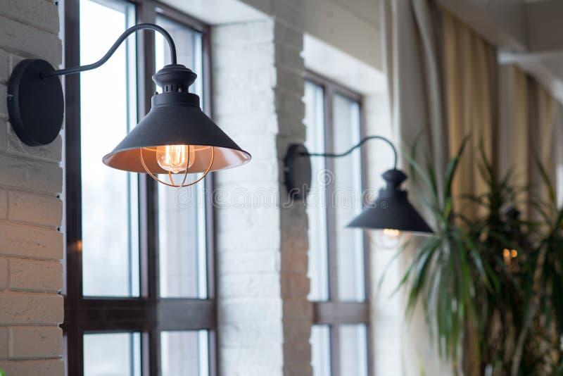 En lampa på bakgrunden av ett fönster och en vägg med gardiner arkivfoton