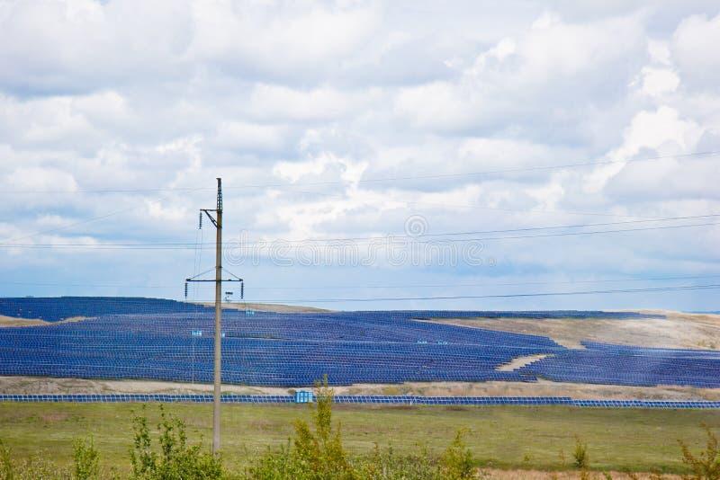 En lantgård av batterier av solenergiväxter på ett fält under en himmel som är full av moln Gr?n elektricitet alternativ energi arkivbilder