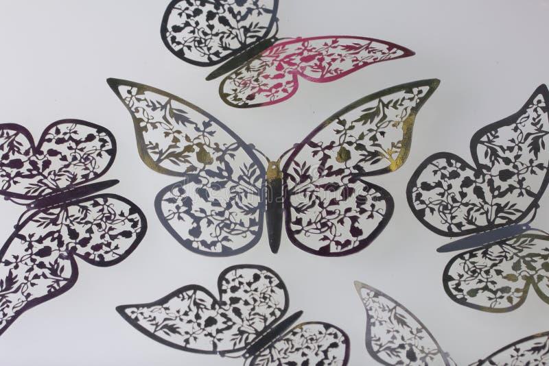 En las decoraciones superficiales blancas de la mentira hechas que de las mariposas cortan de hoja libre illustration