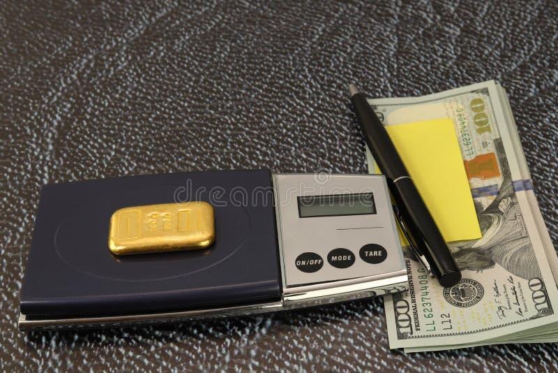 En las escalas miente una barra de oro de cientos gramos Un paquete de papel de los dólares, de la pluma y de nota foreground fotos de archivo libres de regalías