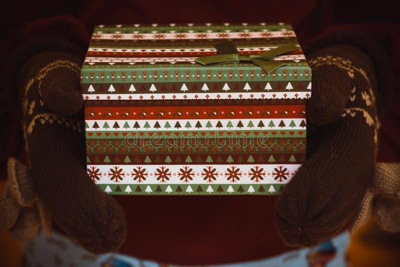 En las manos apacibles en las cuales están llevando las manoplas calientes que sostienen una caja del Año Nuevo en la cual un reg fotografía de archivo
