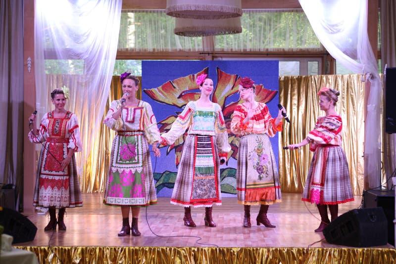 En las muchachas hermosas de la etapa en trajes rusos nacionales, sundresses de los vestidos con el bordado vibrante - grupo de l imagen de archivo