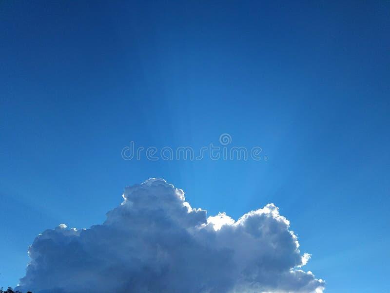 En las nubes brillantes del cielo azul imagenes de archivo