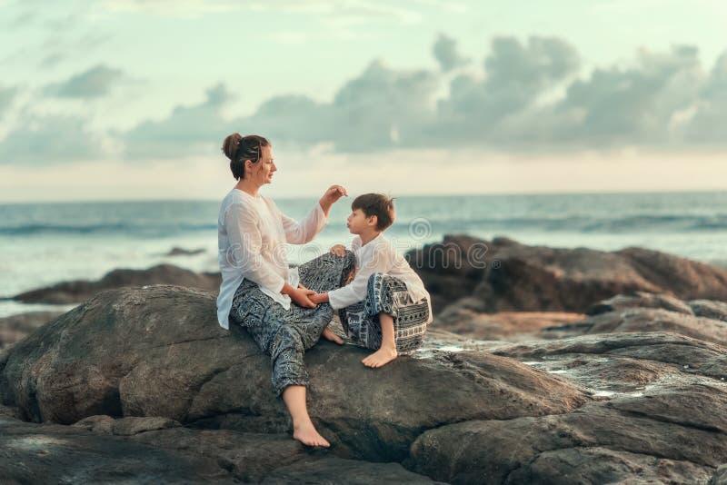 En las piedras del mar, de la madre y del hijo foto de archivo